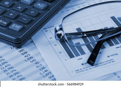 Calculator and Glasses over Business Financial Reports