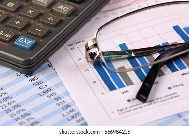 Calculator and Glasses over Financial Reports