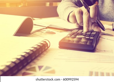 Calculator with hand woman pressing button and thinking about problem for expenses at home office.