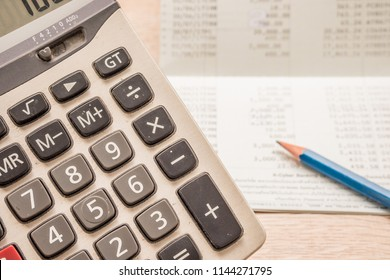 The calculator has a backdrop as a bank book and pencil, placed on a wooden desk.