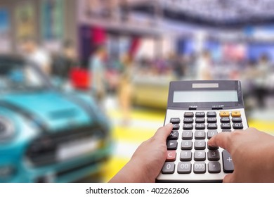 The calculator hold by man's hand and car in background , digital effect abstract for background
