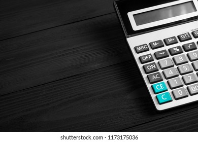 the calculator isolated on a black wooden background