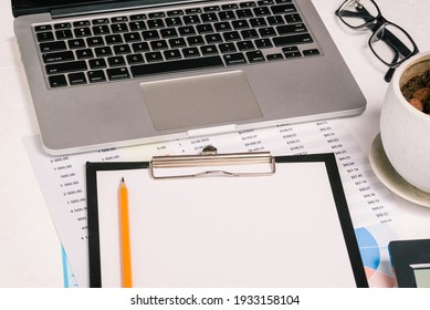 Calculator, laptop and charts. Audit, analytics and banking. Blank sheet of paper for text on the desktop. Research and analytics. Business concept