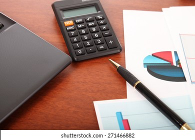 Calculator, laptop and financial documents on the table