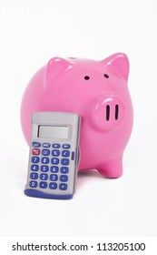 Calculator leans to pink piggy bank, isolated on white background.