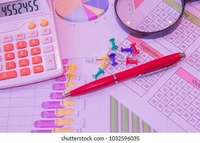 Calculator, magnifier and pen on business documents, accounting and finance concept