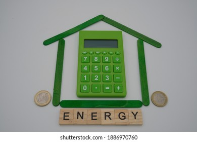 A calculator in the middle of a small house, made up of green sticks, with two coins and a wooden inscription, energy. Ecological economy concept