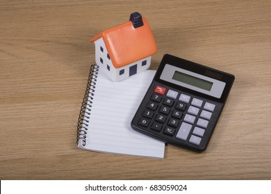 Calculator, model house and blank notepad on a wooden desk in a concept of costs of property ownership, purchase, maintenance and renovations