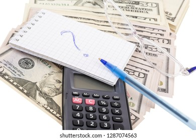 A calculator and notebook with question mark on background with American dollars isolated over white