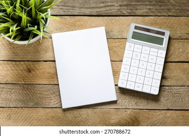 Calculator, notepad and green plant. Calculator, notepad and green plant on wooden background