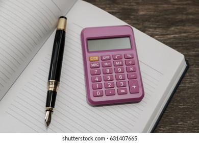Calculator and Notepad on the background of old wood