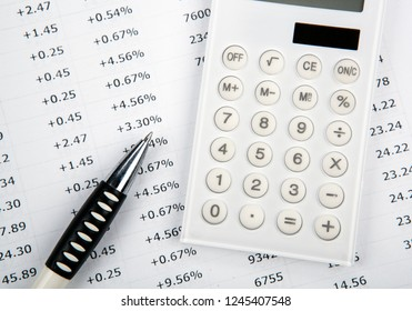 calculator with numbers and pen on the desktop top view