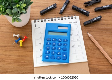 Calculator on calendar with pen on wooden table
