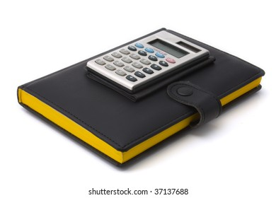 Calculator on a diary. The diary in black leather cover with bright yellow pages