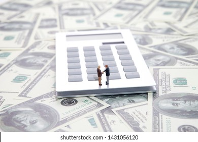 Calculator on the dollar,with two businessman handshaking