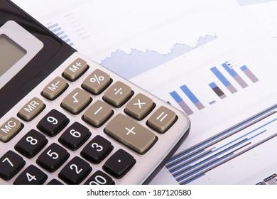 Calculator on financial data graphs.