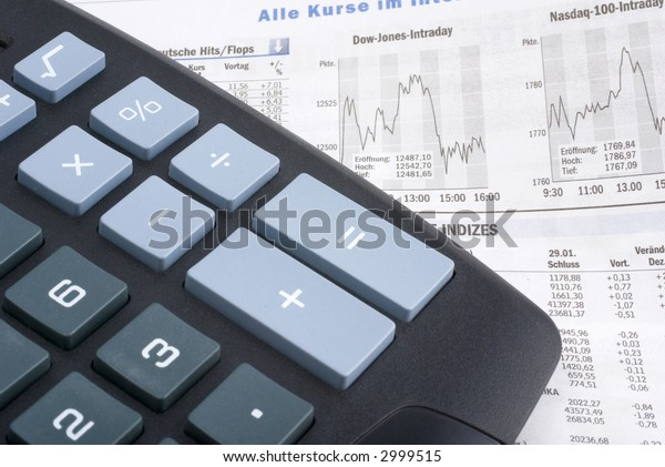 calculator on a financial newspaper showing stock market graphs