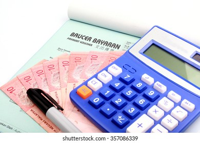 calculator on Malaysian bank note, pen and voucher open book