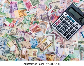 Calculator on mixed banknotes background, close up