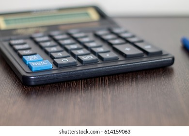 Calculator on a wood table.
