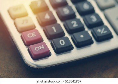 calculator on wood table focus at on press button