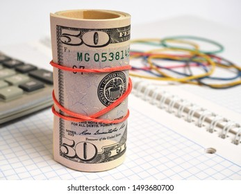 Calculator, pack of dollars and a bunch of rubber bands for money