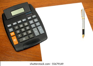 calculator, paper and pens on the table