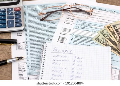 Calculator and pen with 1040 tax form
