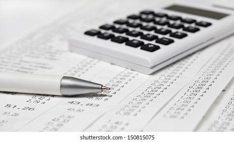 A calculator, a pen, bills, receipts