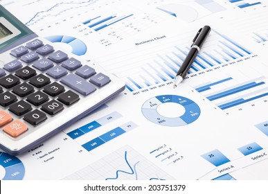calculator and pen with blue business charts, graphs, information and reports background for financial and business concepts