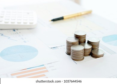 Calculator pen and  coins on financial report.