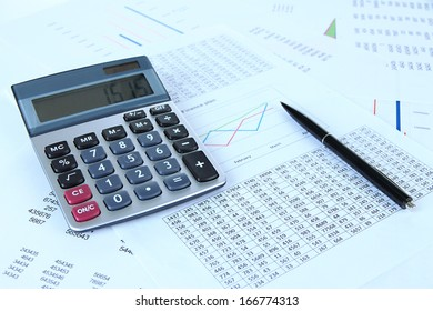 Calculator and pen with documents close up