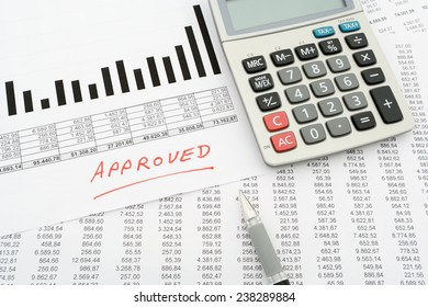 "calculator, pen, documents with numbers and diagram with handwritten text ""approved"""