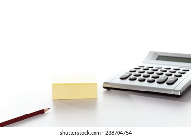 calculator and pen with note on white background