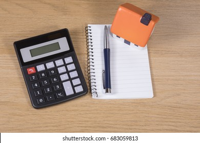 Calculator, pen and notebook and toy house on a wooden desk in a concept of planning, dreams, success, finances and mortgage