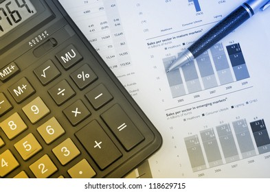 Calculator and pen on annual report
