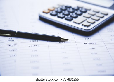 calculator and pen  on document on table