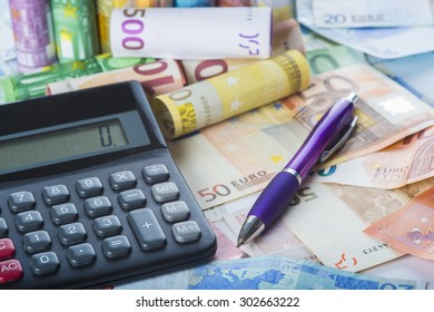 Calculator and pen on a money background made of banknotes