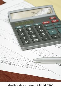 Calculator and pen on top of financial reports