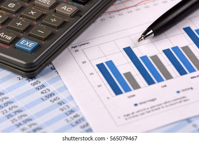 Calculator and Pen over Business Financial Reports