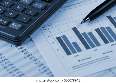 Calculator and Pen over Business Financial Reports in Blue