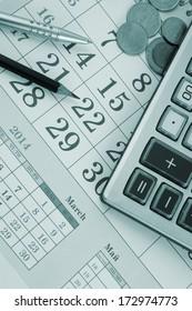 Calculator, pen, pencil  and coins on calendar background