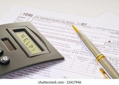 """A calculator and a pen rest on federal tax forms. The calculator screen spells, """"Help!"""""""