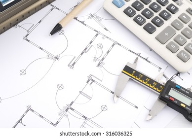 Calculator and pen and vernier caliper and water level on plans