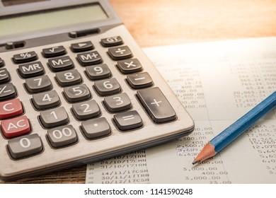 Calculator, pencil, bankbook Put on a wooden table.