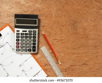 calculator and pencil and ruler and plans on wood table with blank space for Your text or image