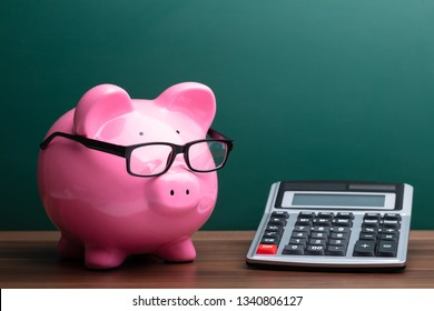 Calculator And Pink Piggybank With Eyeglasses In Front Of Green Board
