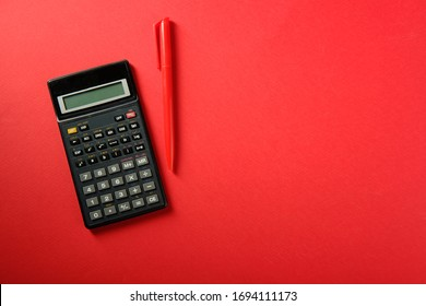 Calculator and red pen on a red background, top view