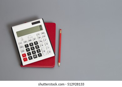 calculator and red pencil on desk