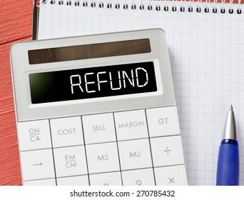 Calculator with refund word. Calculator with refund word and notepad, pen on background